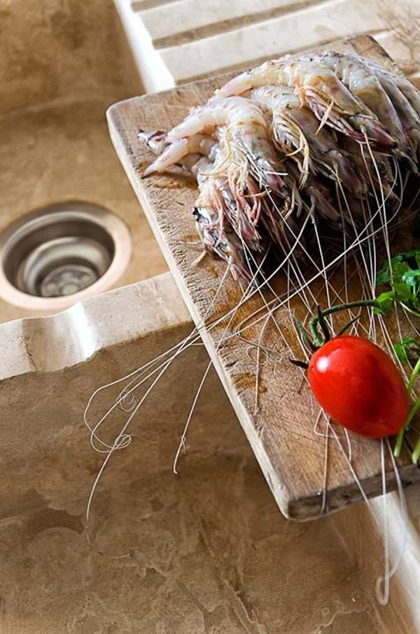 Gamberi freschi in cucina rustica in muratura e travertino