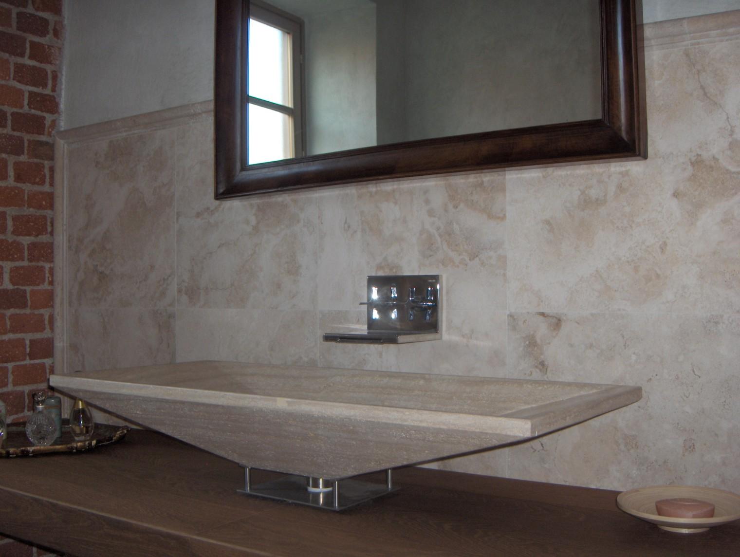 in questo bagno sono stati scelti materiali naturali come la pietra e il legno il lavabo ha una forma rettangolare e la pesantezza della pietra mitigata