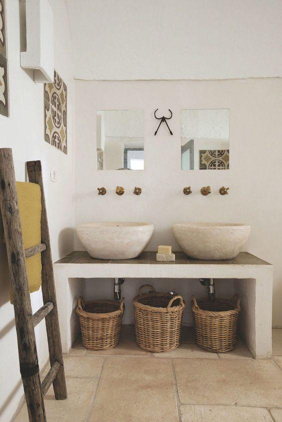 bagno rustico estivo con lavandini in travertino e cesti di paglia